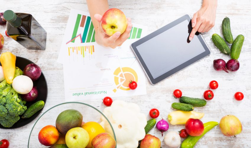 Close-up of a young adult woman informing herself with a tablet PC about nutritional values of fruits and vegetables.