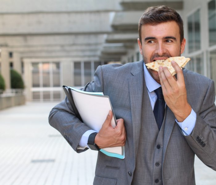 Businessman eating a sandwich on the go.