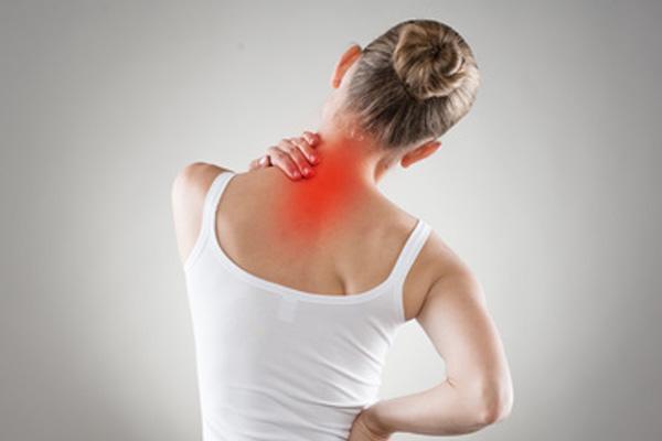 Eine junge Frau leidet unter Nackenschmerzen