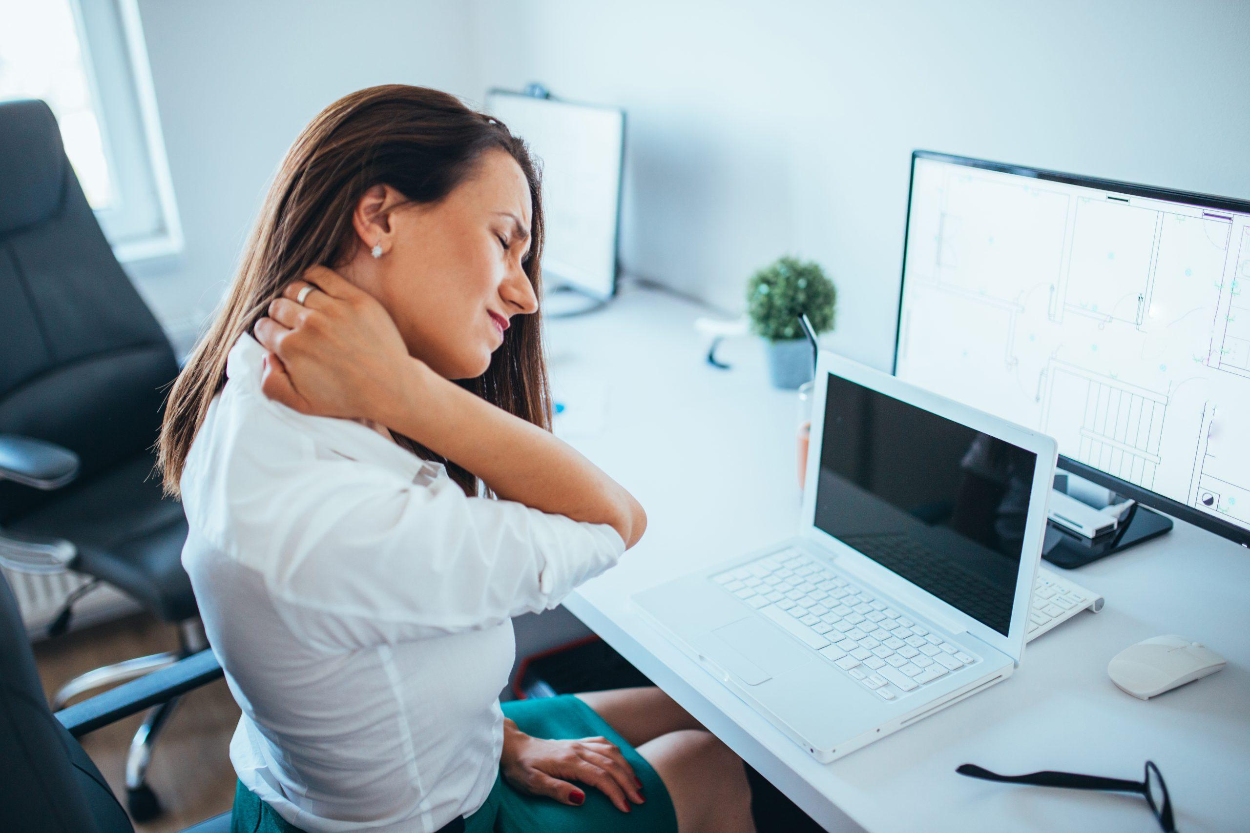 Eine junge Geschäftsfrau leidet unter Nackenschmerzen