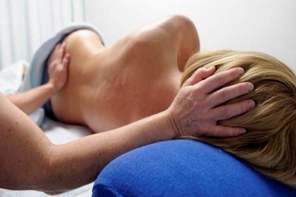 Patientin liegt seitlich auf einer Physiotherapie-Liege und wird behandelt