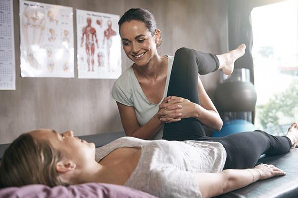Physiotherapeutin behandelt Patientin auf einer Liege
