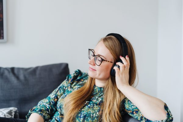 Side view of a young woman daydreaming with closed eyes while listening to relaxing music through black over-ear headphones at home